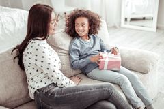 Attractive nice woman sitting on the sofa together with a girl stock photo