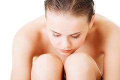 Attractive nude woman sitting holding herself. Closeup. Royalty Free Stock Photography