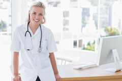 Attractive nurse leaning on desk Royalty Free Stock Photography