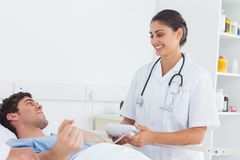Attractive nurse measuring the blood pressure of a patient Stock Image