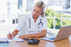 Attractive nurse working in her office Stock Images