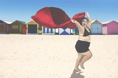 Obese woman with scarf at coast. Attractive obese woman wearing swimwear and running at the coast while holding a red scarf Royalty Free Stock Image