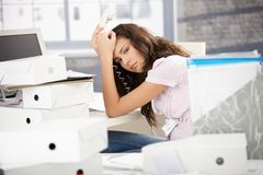 Attractive office worker fed up with work. Attractive young office worker is fed up with work, sitting at desk Royalty Free Stock Images