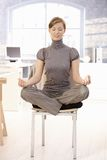 Attractive office worker meditating in office Stock Photos