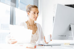 Attractive office worker sitting at desk Stock Photo