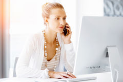 Attractive office worker sitting at desk Royalty Free Stock Image