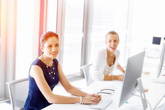 Attractive office worker sitting at desk Stock Photos