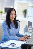 Attractive office worker using laptop Stock Photo