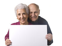 Attractive older couple holding blank billboard. Portrait of a happy older couple holding blank billboard against white background stock image