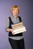 Attractive older lady carrying stack of books Royalty Free Stock Photos