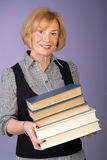 Attractive older lady holds stack of books Royalty Free Stock Photography