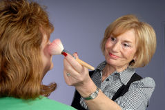 Attractive older lady make up artist Stock Photography