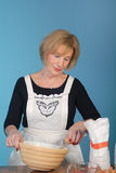 Attractive older lady preparing food Royalty Free Stock Images
