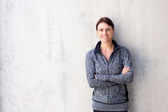 Attractive older sports woman smiling. Portrait of an attractive older sports woman smiling against white wall Stock Photo