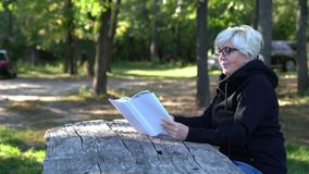 Attractive older woman reading a book in a park. Seated at an old rustic wooden table stock footage