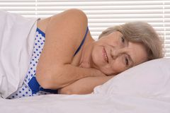 Attractive older woman resting in the bedroom Stock Image