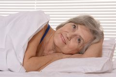 Attractive older woman resting in the bedroom Royalty Free Stock Images
