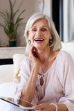 Attractive older woman sitting at home smiling with digital tablet. Portrait of attractive older woman sitting at home smiling with digital tablet stock photos