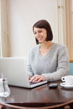 Attractive older woman smiling with laptop at home Stock Photography