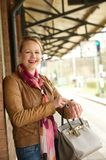 Attractive older woman smiling and pointing to her watch Royalty Free Stock Photography