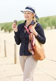 Attractive older woman standing at the beach Stock Photos