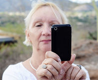 Attractive older woman taking a photo Stock Photography