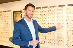 Attractive optician working in his glasses shop Stock Photography