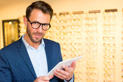 Attractive optician working with tablet in his glasses shop Royalty Free Stock Photography