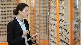 Attractive optician working with tablet in optics stock footage