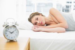 Attractive peaceful woman lying resting in her bed under the cover Royalty Free Stock Image