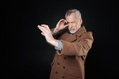 Attractive pensioner looking narrowly into fictitious telescope. It is so far. Handsome retired bearded male keeping his left eye closed pressing lips, standing Stock Photography