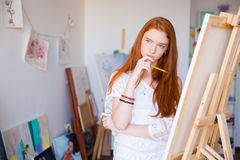 Attractive pensive female artist thinking and drawing on canvas. Attractive pensive female artist with beautiful long red hair thinking and drawing on canvas in royalty free stock images