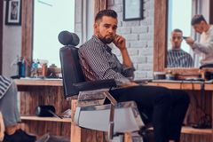 Attractive pensive man is waiting for his turn to get a haircut at busy barbershop. Attractive pensive men is waiting for his turn to get a haircut at busy royalty free stock image
