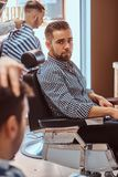 Attractive pensive man is waiting for his turn to get a haircut at busy barbershop. Attractive pensive men is waiting for his turn to get a haircut at busy royalty free stock images