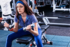 Attractive pensive woman in sportswear lifting some weights Stock Image