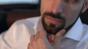 Attractive pensive young man looking to the side stroking his beard. stock video