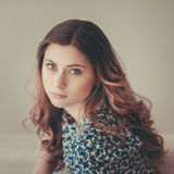 Attractive pensive young woman with long curly red hair. Indoor portrait with soft focus. Vintage faded toning, instagram filters royalty free stock photography