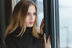 Attractive pensive young woman looking out of the window Stock Photography