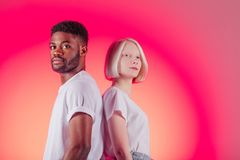 Attractive people in whilte T-shirts looking at the camera. Close up photo. isolated pink background, copy space stock image