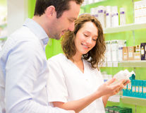 Attractive pharmacist advising a patient. VIew of an Attractive pharmacist advising a patient Stock Image