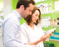 Attractive pharmacist advising a patient Royalty Free Stock Images