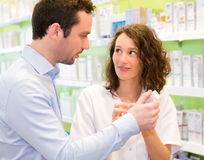 Attractive pharmacist advising a patient Stock Photos
