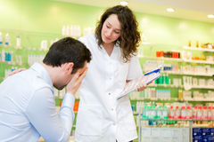 Attractive pharmacist comfort a customer suffering Stock Photo