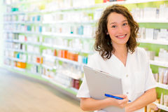 Attractive pharmacist taking notes at work Royalty Free Stock Photography