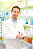 Attractive pharmacist taking notes at work Royalty Free Stock Images
