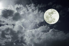 Attractive photo of a nighttime sky with cloudy and bright full moon. Beautiful nature use as background. Outdoors.  Royalty Free Stock Images