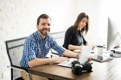 Man editing photos with a coworker Stock Photo