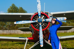 Attractive pilot in helmet standing with airplane Royalty Free Stock Photos