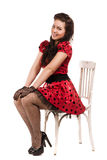 Attractive pin-up girl. Sitting on a chair stock image