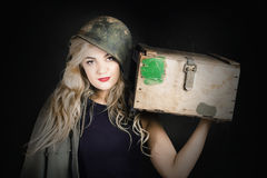Attractive pinup girl. Blond bombshell. Dark retro army picture of an attractive young pinup soldier girl in cadet hat standing with ammunition supply box. Blond Royalty Free Stock Image